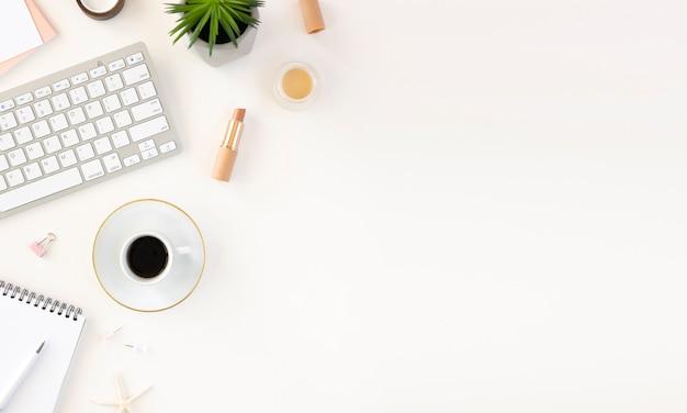 Mesa de trabalho feminina mínima com teclado, notebook e café