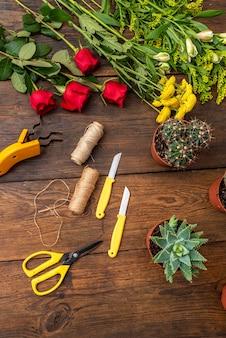 Mesa de trabalho marrom com flores e acessórios de floricultura, vista de cima