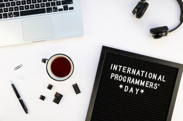 Mesa de trabalho mínima com laptop e chá para o dia dos programadores