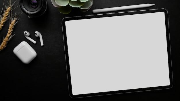 Mesa de trabalho mínima escura, tablet gráfico, maquete de tela vazia, vista superior close-up