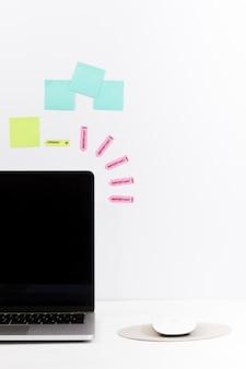 Mesa de trabalho minimalista arranjada com laptop e notas na parede