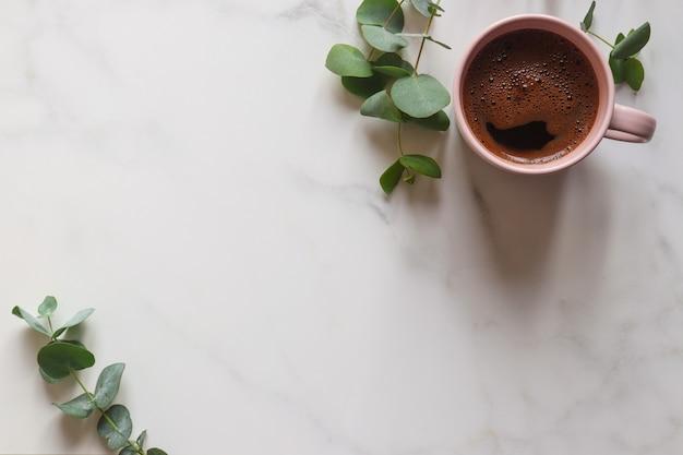 Mesa de trabalho minimalista em mármore com folhas de eucalipto e xícara de café com espaço de cópia
