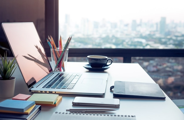 Mesa de trabalho moderna com laptop e vista panorâmica da cidade da janela