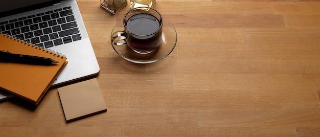 Mesa de trabalho na moda com espaço de cópia, laptop, xícara de café e artigos de papelaria na mesa de madeira