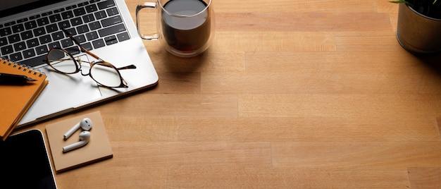 Mesa de trabalho na moda com espaço de cópia, laptop, xícara de café e suprimentos na mesa de madeira