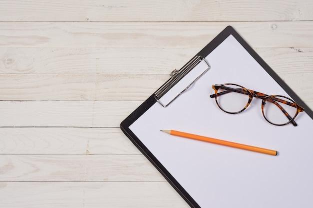 Mesa de trabalho, papelaria, pasta de papel, escritório, óculos e fundo de madeira