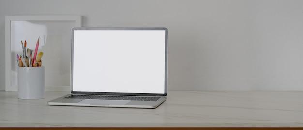 Mesa de trabalho simples com laptop de tela em branco, ferramentas de pintura, espaço de moldura e cópia