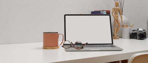 Mesa de trabalho simples com mock-se laptop, óculos, caneca e suprimentos na mesa branca com cadeira branca