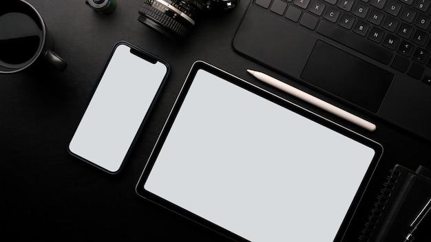 Mesa de trabalho tela em branco tablet e maquete de smartphone com câmera laptop café fundo preto