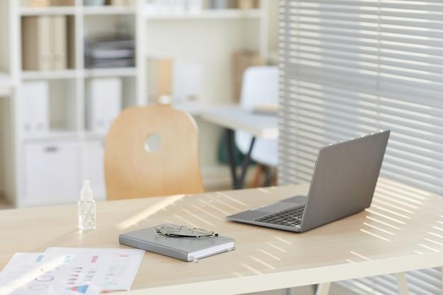 Mesa de trabalho vazia com laptop e desinfetante para as mãos iluminada pela luz do sol em um escritório pós-pandêmico moderno
