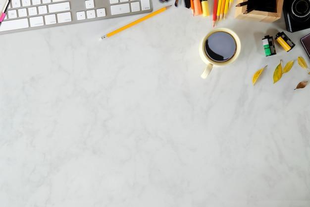 Mesa de trabalho vista superior com suprimentos de teclado e fotógrafo