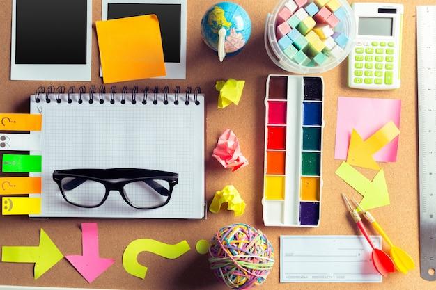Mesa de um artista com muitos objetos de papelaria