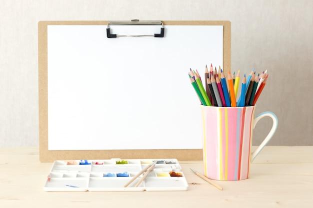 Mesa de um artista com pranchetas de objetos de papelaria. studio atirou em fundo de madeira.