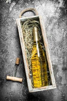 Mesa de vinho. uma garrafa de vinho branco em uma velha caixa. sobre uma mesa rústica.