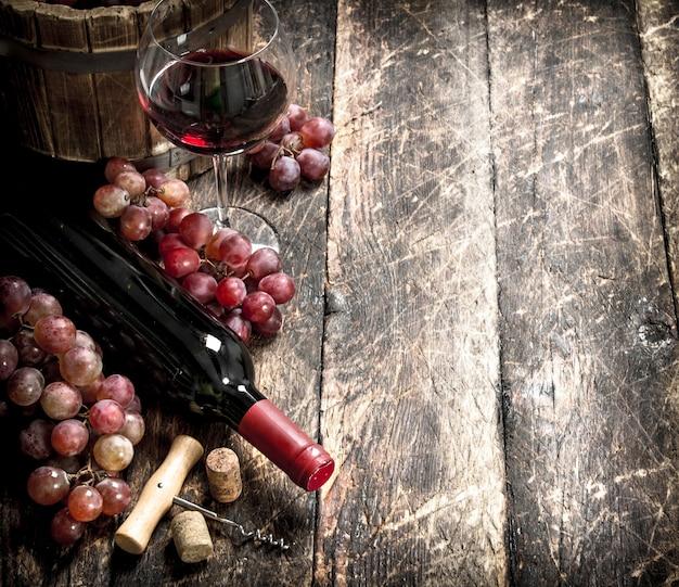 Mesa de vinho. vinho tinto com taças com uvas. em uma mesa de madeira.