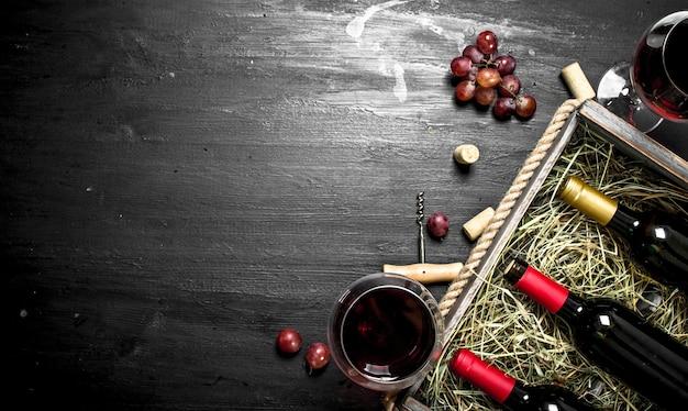 Mesa de vinho. vinho tinto em uma velha caixa com um saca-rolhas. no quadro negro.