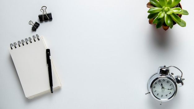 Mesa de vista superior com bloco de notas e relógio