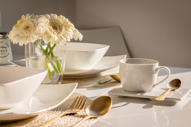 Mesa decorada na cozinha com garfo de ouro, colheres e faca e flores. mesa posta. configuração de mesa. preparando-se para um banquete. ainda vida