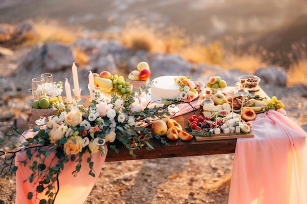 Mesa decorada para festa de casamento com buquê de rosas brancas, frutas e bolo