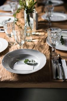 Mesa decorada pronta para o jantar. lindamente decorado, conjunto de mesa com flores, velas, pratos e guardanapos para casamento ou outro evento no restaurante.