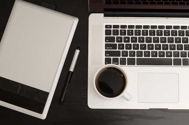 Mesa digitalizadora com um lápis, parte do caderno e uma xícara de café em uma mesa de madeira preta, close-up