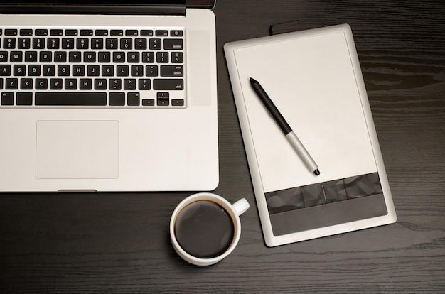 Mesa digitalizadora com um lápis, teclado de laptop e xícara de café em uma mesa de madeira preta