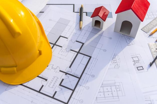 Mesa do arquiteto com o edifício da construção do modelo e do capacete de segurança.