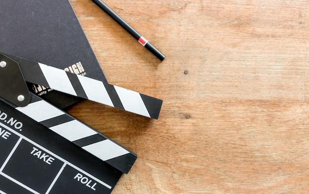Mesa do diretor de cinema. ripa, livro e câmera digital na mesa de madeira