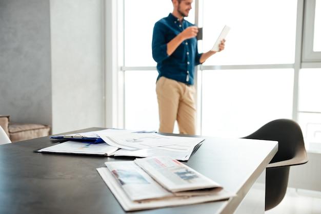 Mesa do empresário com documentos e jornais e o jovem empresário em pé perto de uma grande janela