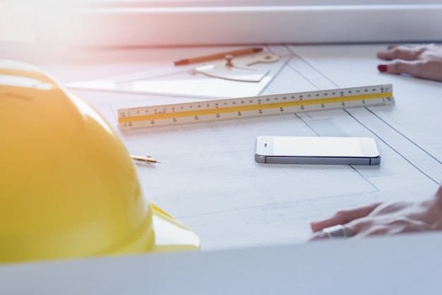 Mesa do engenheiro designer e arquiteto no escritório com equipamentos e papel de desenho para o plano de trabalho no entardecer