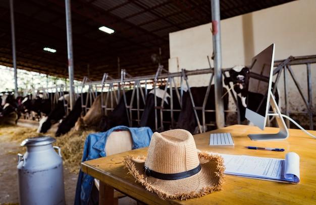 Mesa do fazendeiro ele usa um computador de relações públicas em vendas de leite