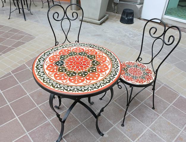 Mesa e cadeira da mobília de jardim no balcão da cafetaria.