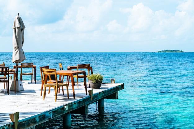 Mesa e cadeira de madeira com vista para o mar nas maldivas