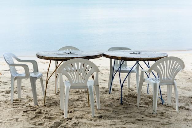 Mesa e cadeira de madeira em areia branca da praia e mar azul em dia de sol