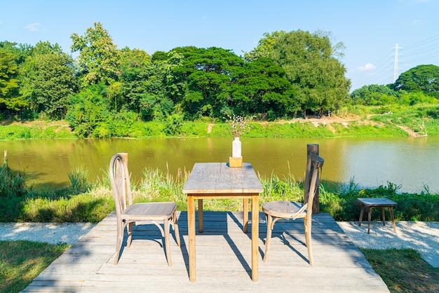 Mesa e cadeira vazias com vista para o rio e céu azul