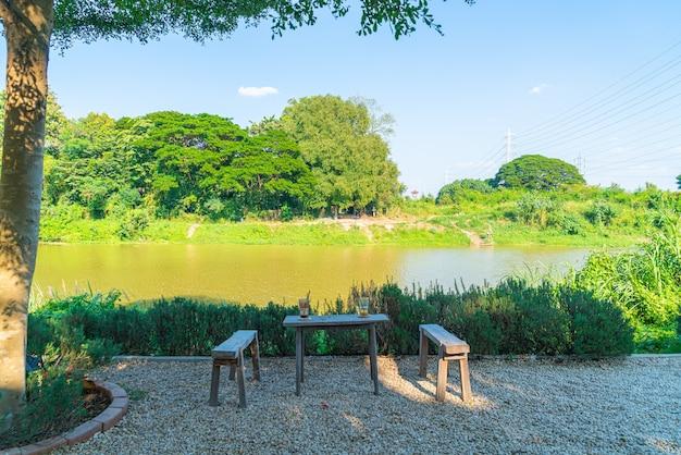 Mesa e cadeira vazias com vista para o rio em cafeteria e restaurante