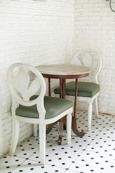 Mesa e cadeira vintage com parede de tijolos brancos