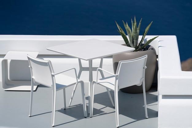 Mesa e cadeiras brancas no terraço em oia, santorini.