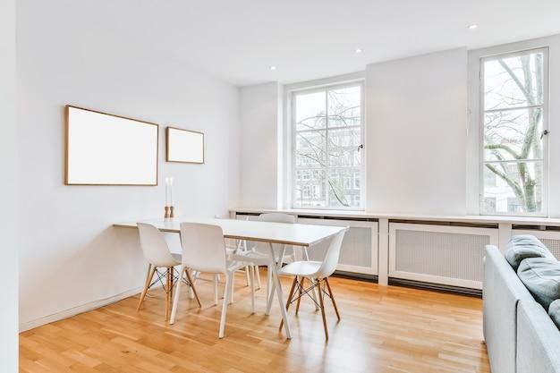 Mesa e cadeiras de estilo minimalista localizadas perto da parede branca com pinturas emolduradas e janelas na sala de jantar clara em apartamento contemporâneo