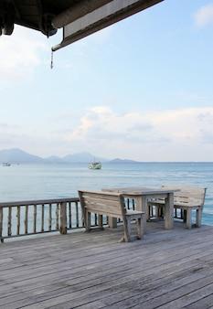 Mesa e cadeiras de madeira em um resort de praia tropical