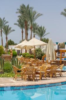 Mesa e cadeiras de vime em um café de praia perto da piscina