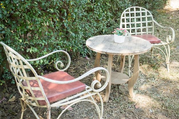 Mesa e cadeiras em pé no jardim com sombras