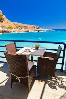 Mesa e cadeiras em um café em frente ao mar azul