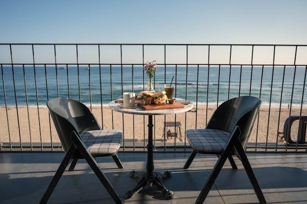 Mesa e cadeiras servidas com frango sandwish, café gelado e vaso de flores no terraço de um café perto da praia