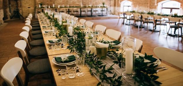 Mesa elegante posta com bela decoração com folhas verdes em restaurante