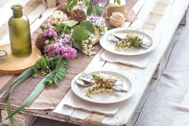 Mesa elegantemente decorada para férias com talheres modernos, arco, vidro, vela e presente