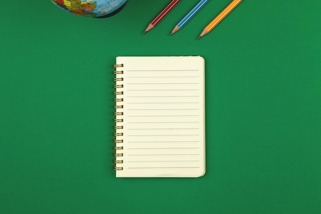 Mesa escolar verde com caderno pautado em branco e foto com vista superior a lápis com espaço de cópia