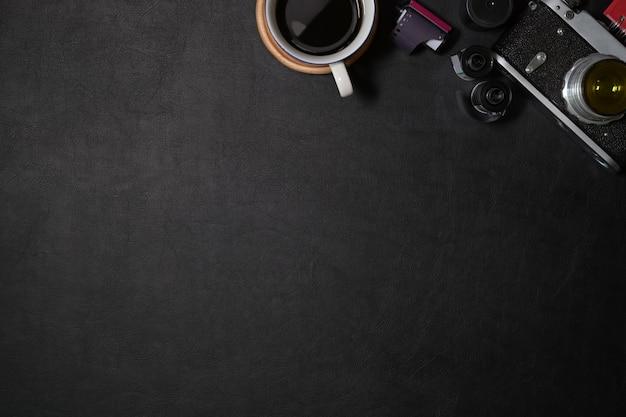 Mesa escura de couro de escritório com câmera vintage, filmes, café e cópia espaço