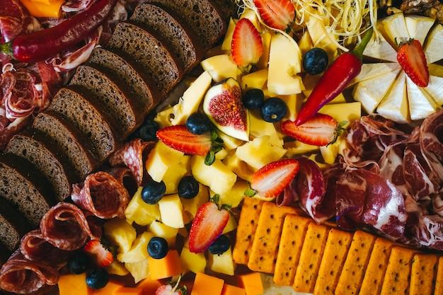 Mesa farta com diversos tipos de petiscos de carnes frias, pão de queijo e frutas