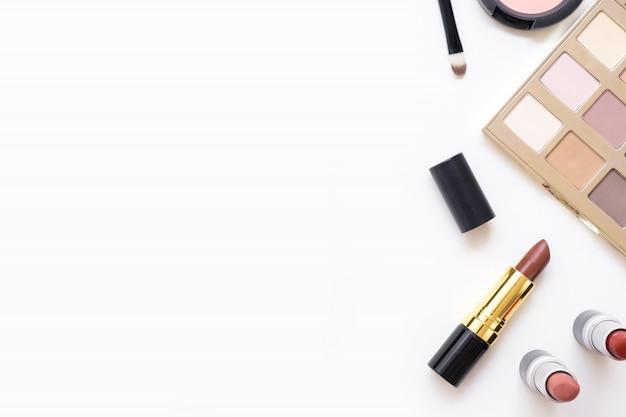 Mesa feminina com maquiagem, incluindo batons, paleta de olho, base, escovas